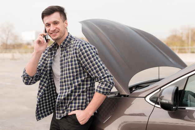 Man with broken car talking over phone Free Photo