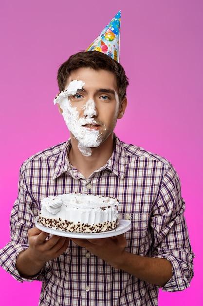 Человек с тортом на лице над фиолетовой стеной. день рождения. Бесплатные Фотографии