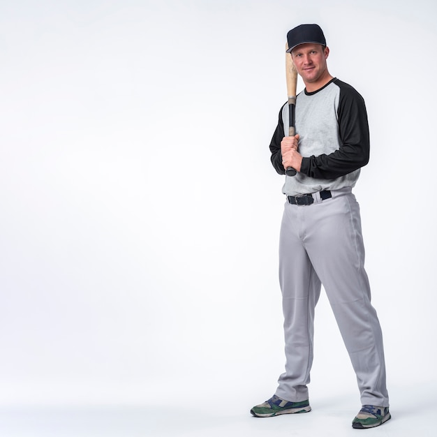 Man with cap posing with baseball Free Photo