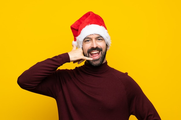 Man with christmas hat over isolated yellow background making phone gesture. call me back sign Premium Photo