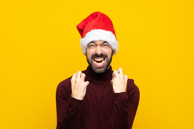 Man with christmas hat over isolated yellow wall frustrated by a bad situation Premium Photo