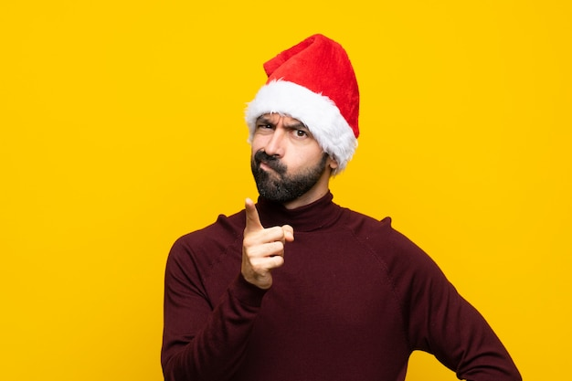 Man with christmas hat over isolated yellow wall frustrated and pointing to the front Premium Photo