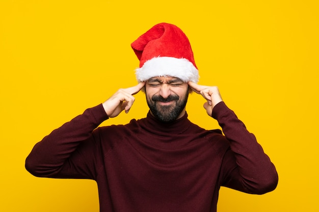 Man with christmas hat over isolated yellow wall with headache Premium Photo