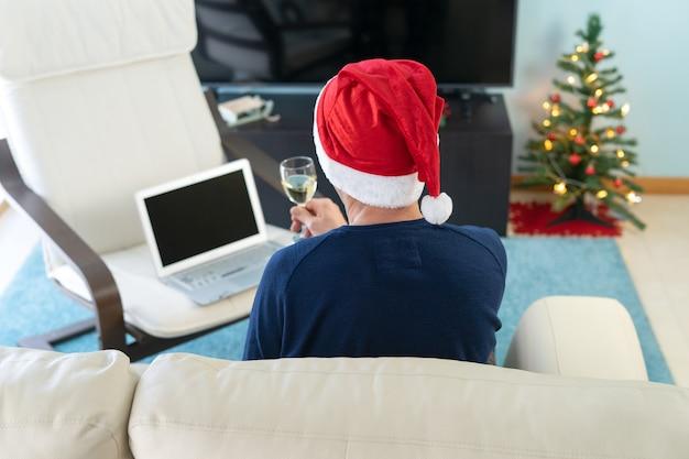 Человек с рождественской шляпой поджаривания перед компьютером. понятие технологии и заключения. Premium Фотографии