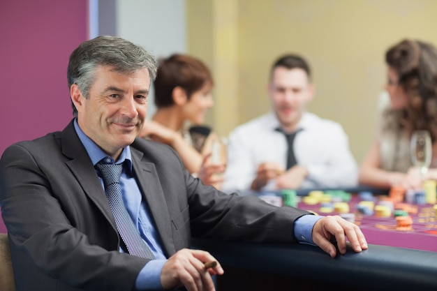 Man with cigar taking break from roulette table Premium Photo