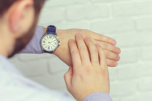Man with clock checks the time Premium Photo