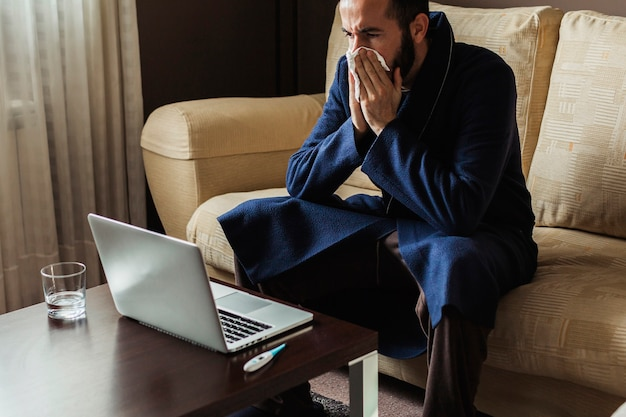 Man with a cold making an online medical consultation with his doctor from home Premium Photo