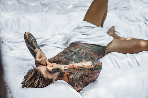 Man with colorful tattoos posing on a white sheet Free Photo