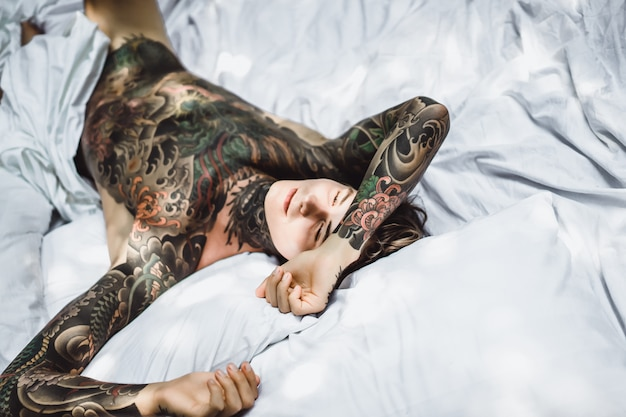 Man with colorful tattoos resting on a white sheet Free Photo