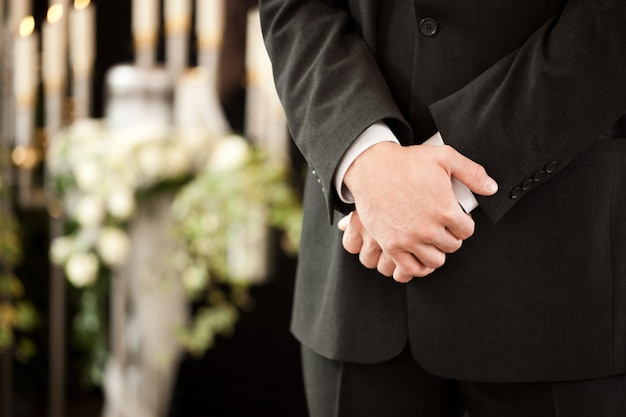 Man with crossed hands at funeral Premium Photo