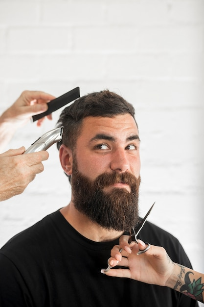 Man with dark hair and long beard gets groomed and trimmed Free Photo