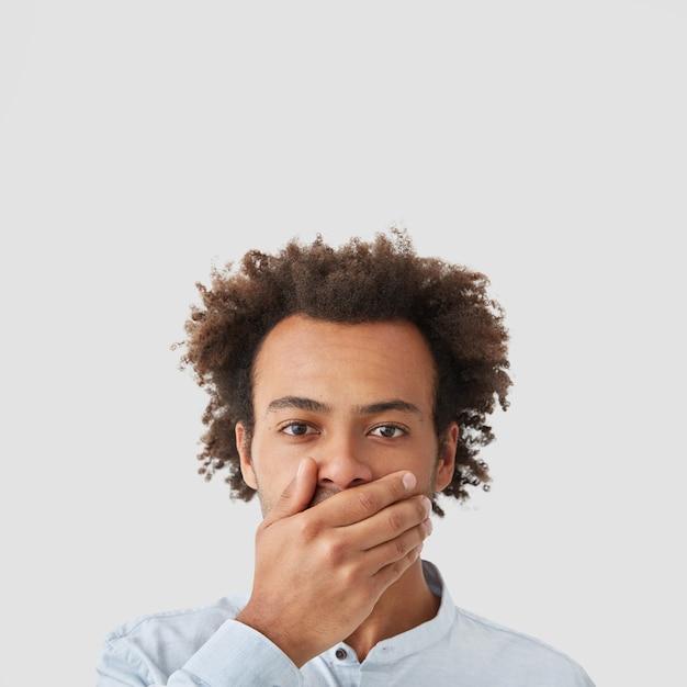 肌の色が濃く、表情が真面目で、口を手で覆い、無言になり、噂を広めない男 無料写真