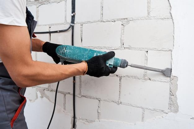壁から漆喰を取り除く解体ハンマーを持つ男 Premium写真