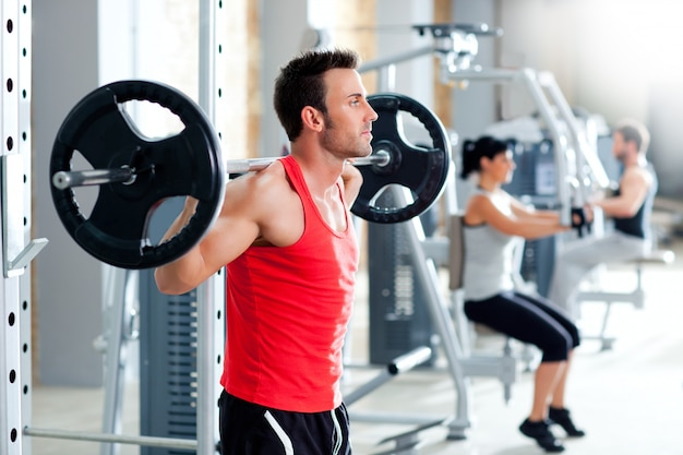 Man with dumbbell weight training equipment  gym Premium Photo