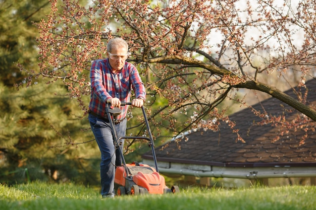 Man with electric lawnmower, lawn mowing. gardener trimming a garden. sunny day, suburb, village. adult man pruning and landscaping garden, trimming grass, lawn, paths. hard work on nature. Premium Photo