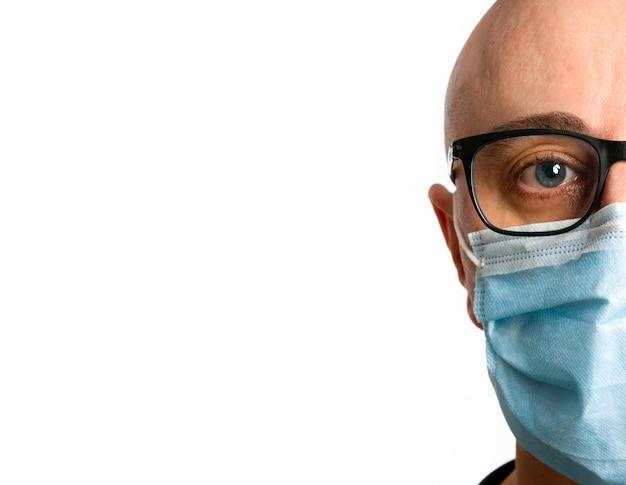 フェイスマスクを持つ男を白で隔離します。 Premium写真