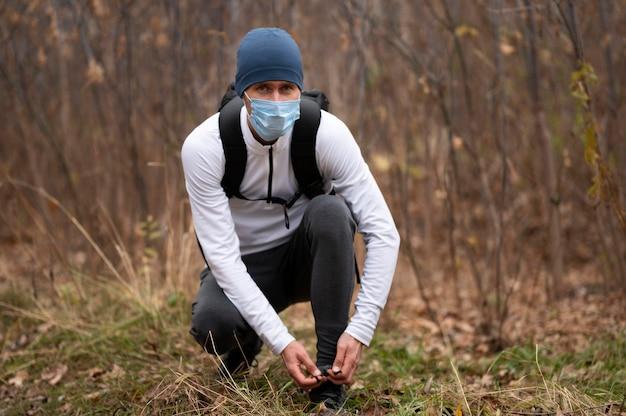Uomo con la maschera per il viso nei boschi legando i lacci delle scarpe Foto Gratuite