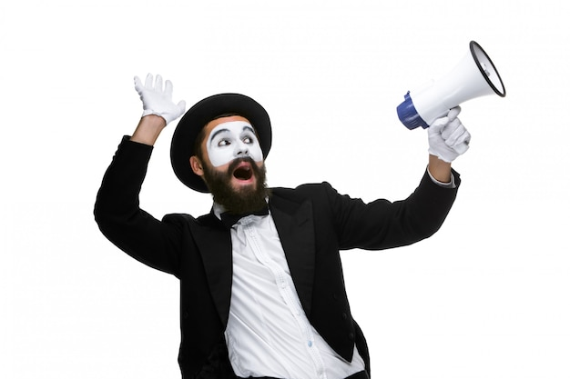 Uomo con un volto mimo urlando nel megafono Foto Gratuite