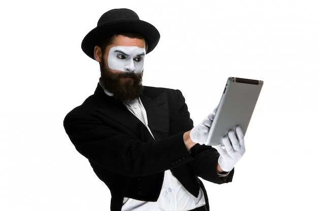 Man with a face mime working on laptop Free Photo