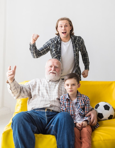 Man with father and son watching football game Free Photo