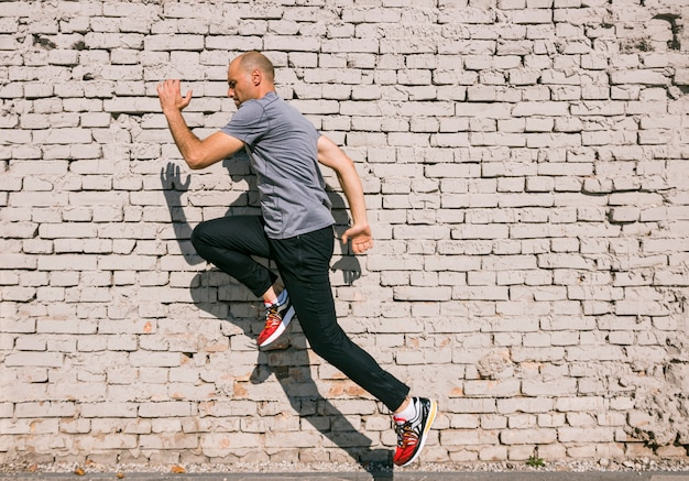 Man with fit body jumping and running against white brick wall Free Photo