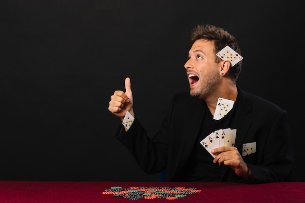 Man with four aces gesturing thumbs up with casino chips on poker table Free Photo