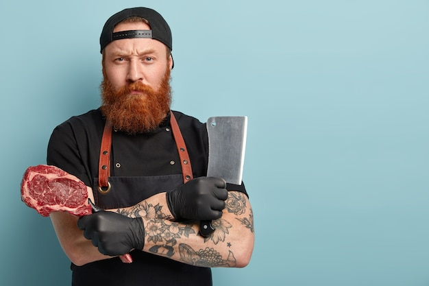 Man with ginger beard in apron and gloves holding knife and meat Free Photo