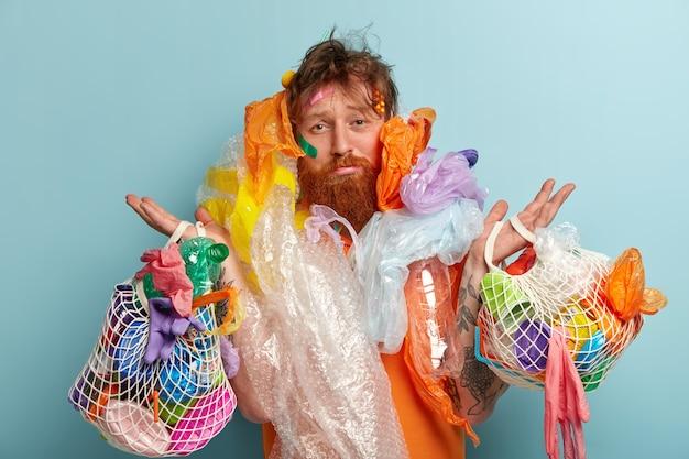 Uomo con barba allo zenzero che tiene i sacchetti con rifiuti di plastica Foto Gratuite