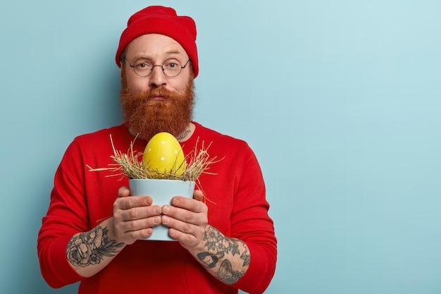 Uomo con la barba allo zenzero che indossa abiti colorati tenendo l'uovo di pasqua Foto Gratuite