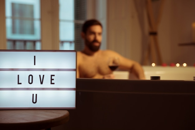 Man with glass of drink in spa tub and i love u title on lamp Free Photo