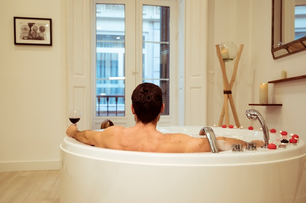Man with glass of drink in spa tub with burning candles Free Photo