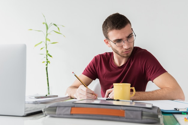 Man with glasses being focused white reading a paper Free Photo