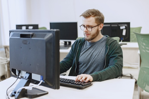 Man with the glasses. student in computer science class. person uses a computer. Free Photo