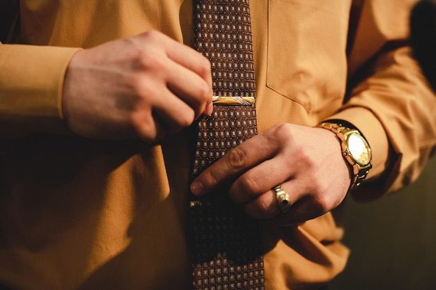 Man with a gold watch adjusts a tie Free Photo