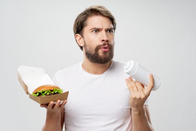 彼の手にファーストフードダイエットホワイトtシャツにゴールドバーグを持つ男 Premium写真