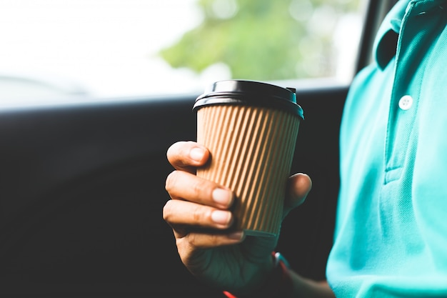 A man with green shirt holding a cup of coffee in the car. Premium Photo