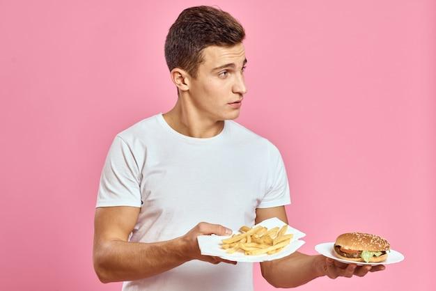 Человек с гамбургером и картофелем фри фастфуд калории розовый космос свежая еда эмоция модель Premium Фотографии