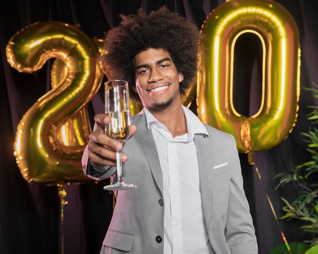 Man with happy new year 2020 balloons and glass of champagne Free Photo