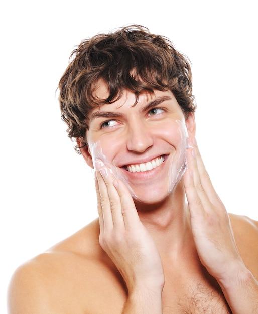 彼の顔のひげそりの後、保湿ローションを適用する幸せな笑顔を持つ男 無料写真