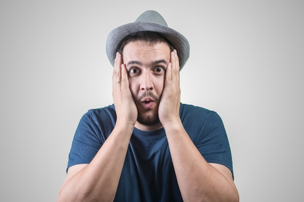 Man with hat surprised with hands on his face Premium Photo