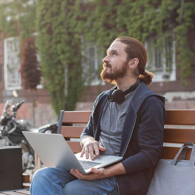 Человек с наушниками и ноутбуком в городе Бесплатные Фотографии
