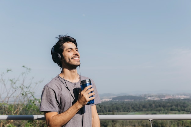 Man with headphones and thermocup Free Photo
