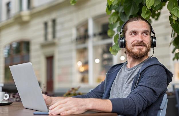 Человек с наушниками на городской террасе с ноутбуком Бесплатные Фотографии
