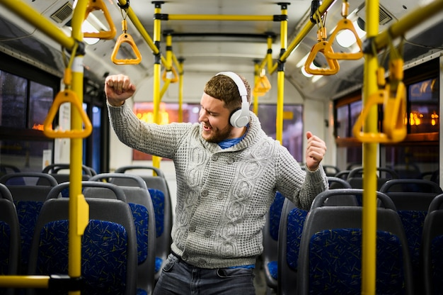 Man with headphones dancing alone in the bus Free Photo