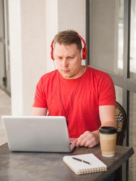 Uomo con le cuffie che mangiano caffè all'aperto e che lavorano al computer portatile Foto Gratuite