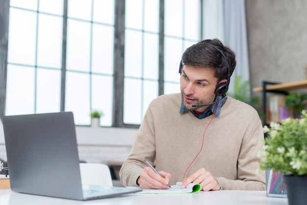 Man with headphones having an online meeting Premium Photo