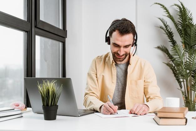 노트북에 영상 통화를 갖는 헤드셋을 가진 남자 무료 사진