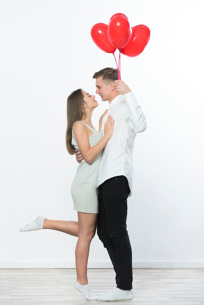 Man with heart balloons hugging woman Free Photo