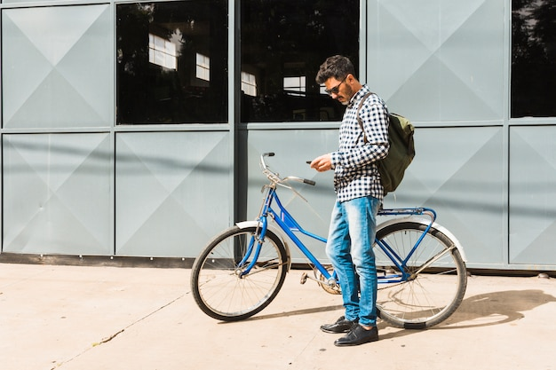 Man with his backpack using mobile phone standing near the bicycle Free Photo