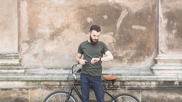 Man with his bicycle looking at time in wrist watch Free Photo